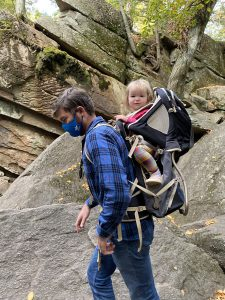 man carrying toddler in hiking backpack