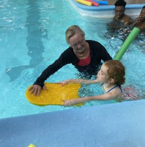 swim instructor with child on boogy board