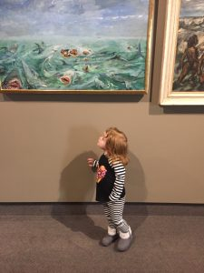 young girl looking at a painting