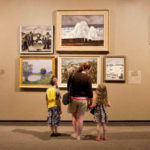 a mother and her two children look at a wall of paintings