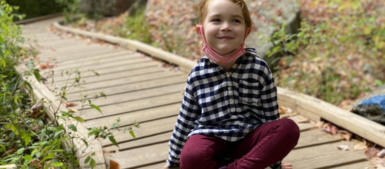 Girl sitting on a wooden path