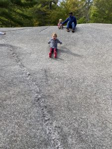 girl sliding down large rock