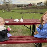 two kids at a picnic table eating ice cream