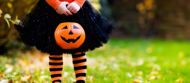 girl dressed in black and orange with a pumpkin pail