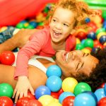child and parent playing in a ball pit
