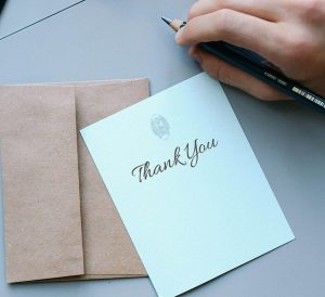 thank you note with envelope and hand holding a pen